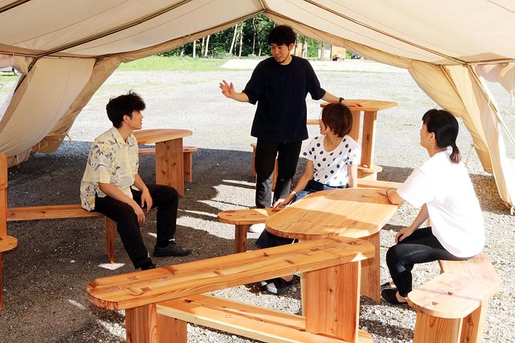 テント内にベンチやテーブルを配置した交流スペースをつくり出し、出来栄えを確かめる学生ら=利賀国際キャンプ場