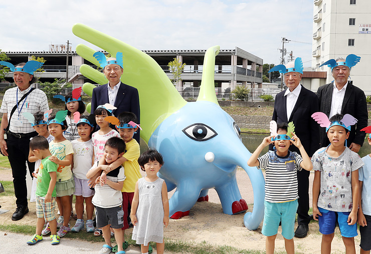 除幕式でモニュメントを披露する石井知事(後列左から2人目)ら=富岩運河環水公園