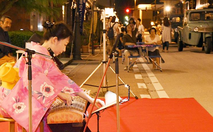 富山銀行本店前で琴の生演奏を披露する太田さん(手前)