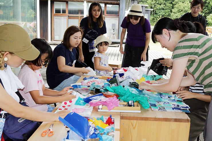 カラフルなレジ袋を組み合わせてバッグを作る参加者たち