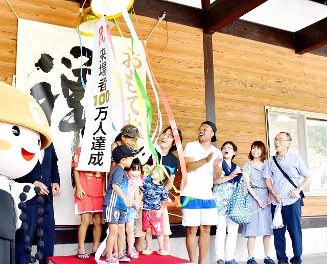 100万人突破のくす玉を割る家族=8月26日、福井県永平寺町の道の駅「禅の里」
