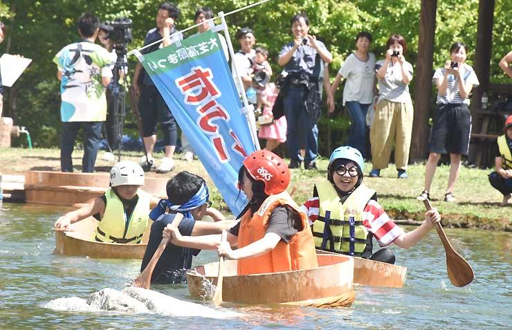 家族や友人が見守る中、湖上でたらいをこぐ参加者たち