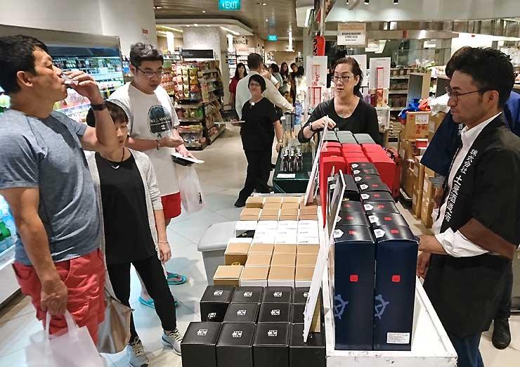 シンガポールの百貨店で主力商品をPRする土屋社長(右)ら