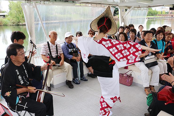 船上で披露される演奏と舞に合わせて手拍子を送る乗客=富岩運河環水公園