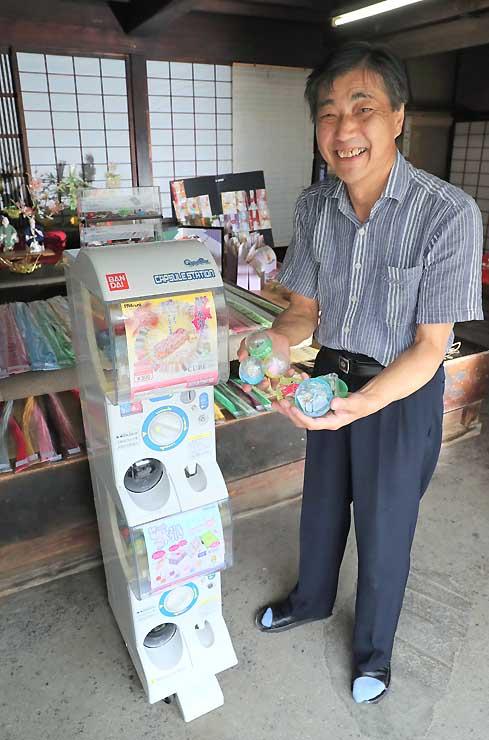 販売機を前にカプセルを手にする田中社長=28日、飯田市今宮町
