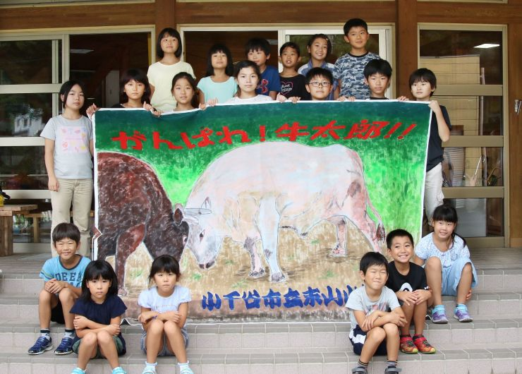 牛太郎の応援旗と制作した児童たち=小千谷市の東山小学校
