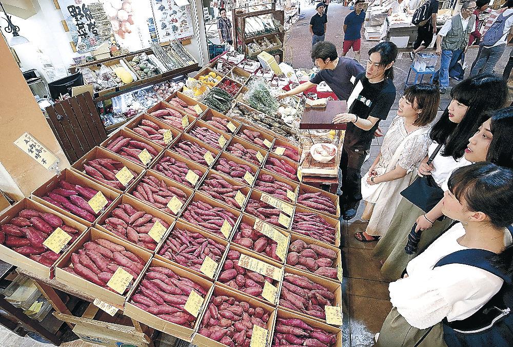 店頭に並んだ五郎島金時を眺める買い物客=近江町市場
