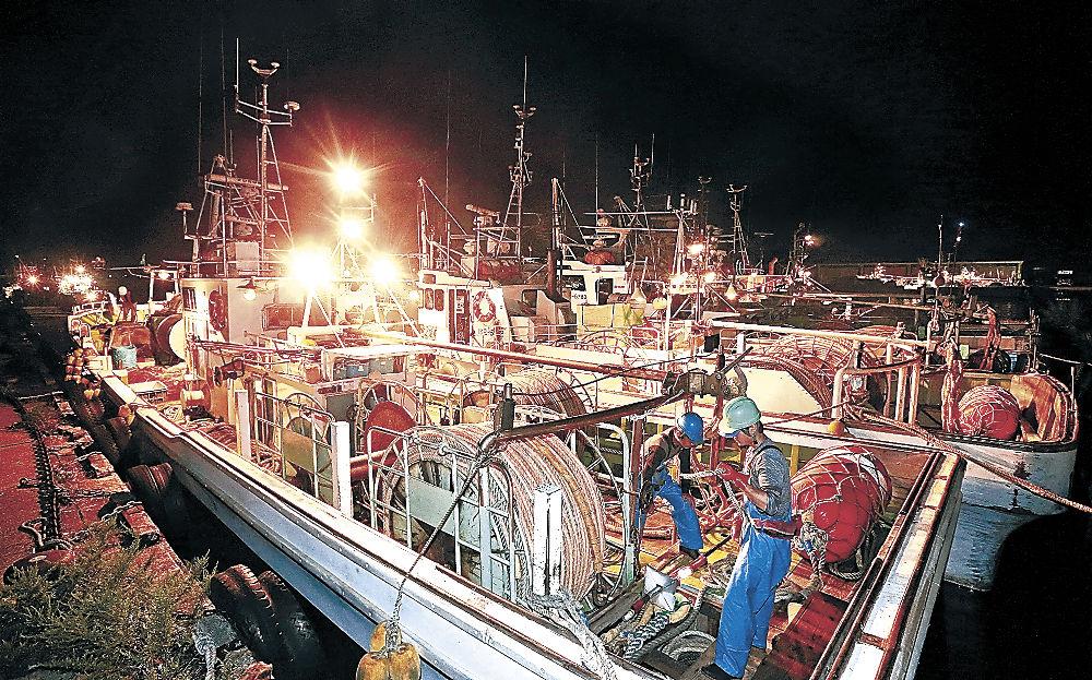 出港を前に準備作業を進める漁師=1日午後10時、金沢港
