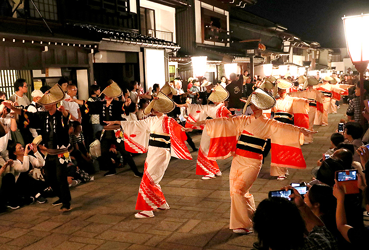 大勢の観光客が見守る中、石畳の通りで町流しする踊り手=1日午後9時20分ごろ、富山市八尾町諏訪町