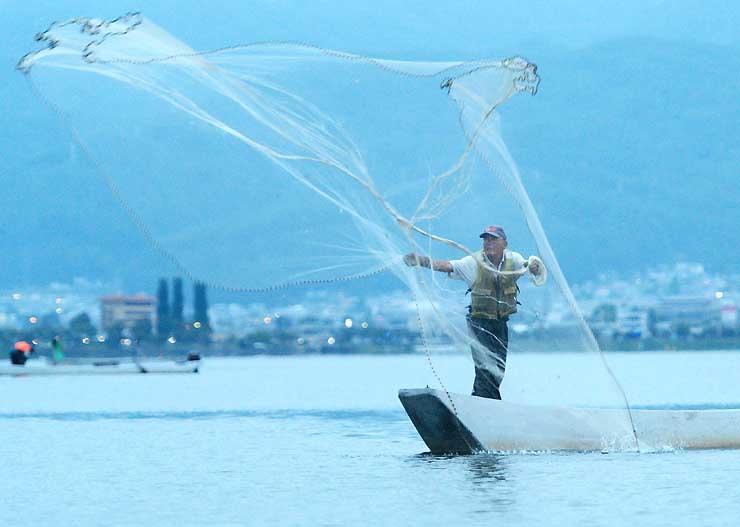 ワカサギの投網漁が解禁され、諏訪湖で網を打つ漁師=3日午前5時15分