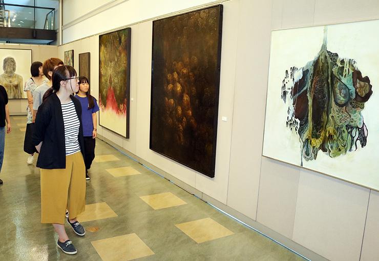 腐敗したリンゴやカボチャなどさまざまなモチーフの油彩画が並ぶ会場=北日本新聞ギャラリー