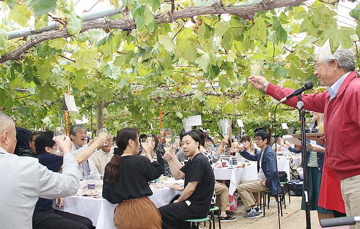ブドウ棚の下、山藤社長(右)の発声で乾杯する参加者