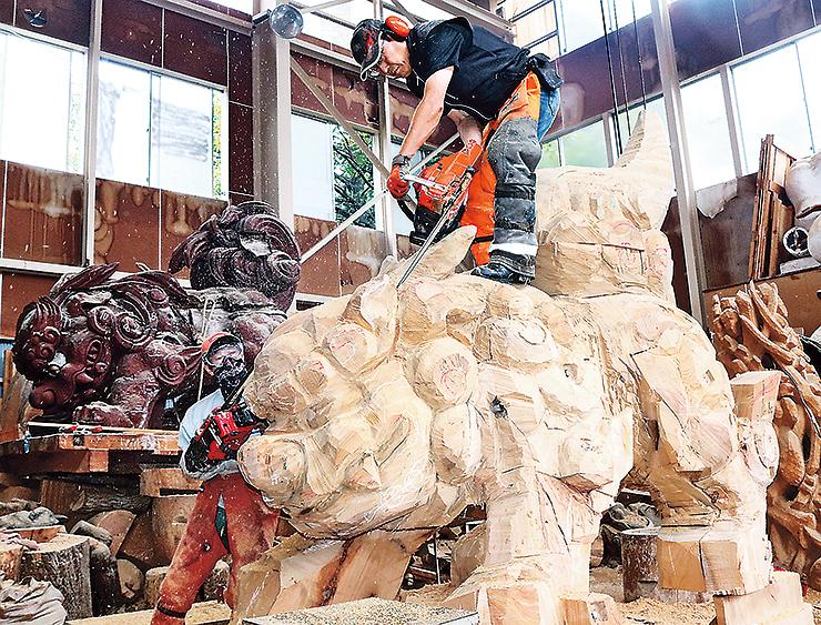 親獅子の彫刻を制作する井波彫刻協同組合役員ら。左後方は老朽化した親獅子