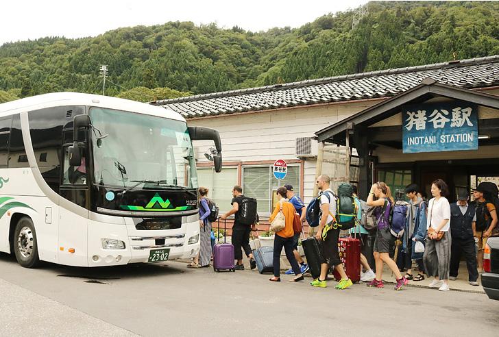 高山方面行きの代行バスに乗り込む観光客=JR猪谷駅