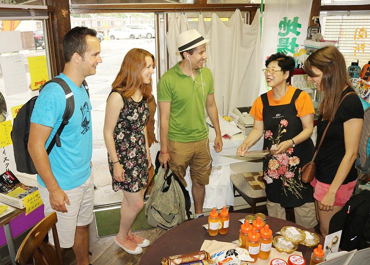 英語表記のメニュー表で外国人観光客に商品を紹介する森下さん(右から2人目)=森下友蜂堂