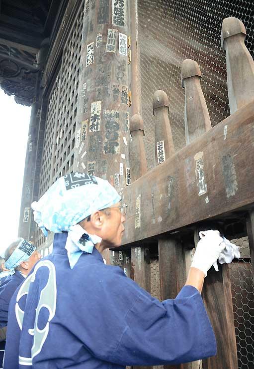 仁王門に貼られた千社札を、ぬれた布を使って剥がす仲見世通りの商店主ら