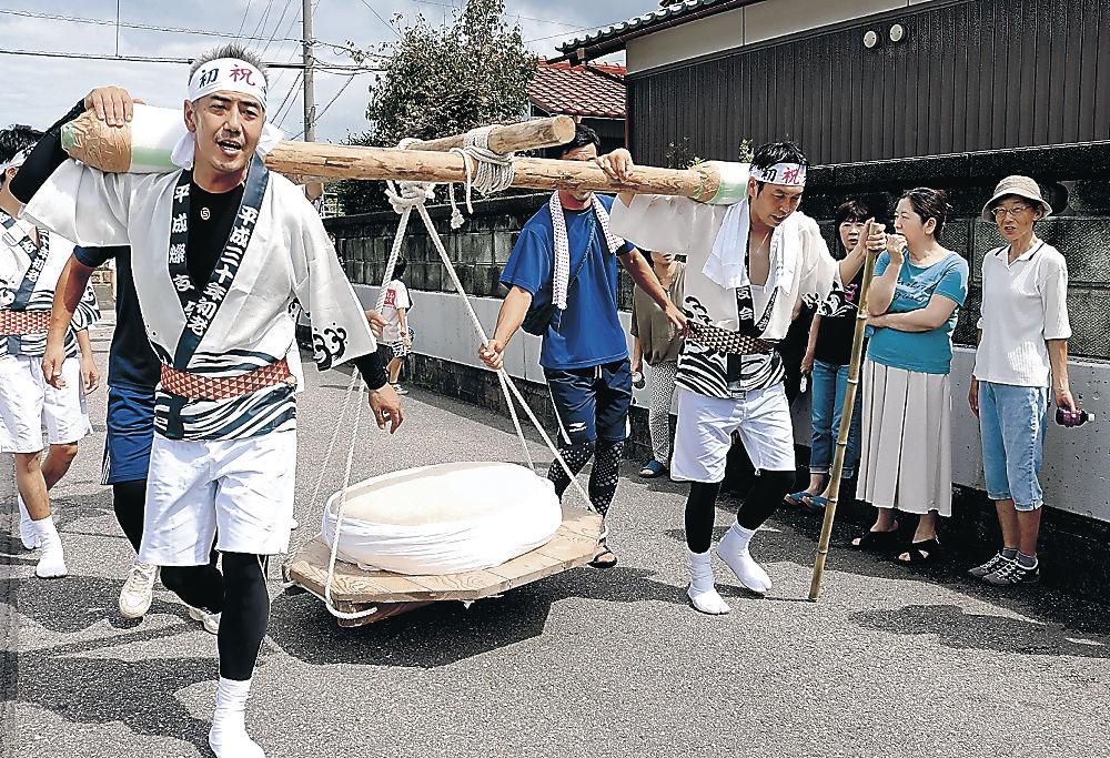 大鏡餅を担いで練り歩く会員=小松市向本折町