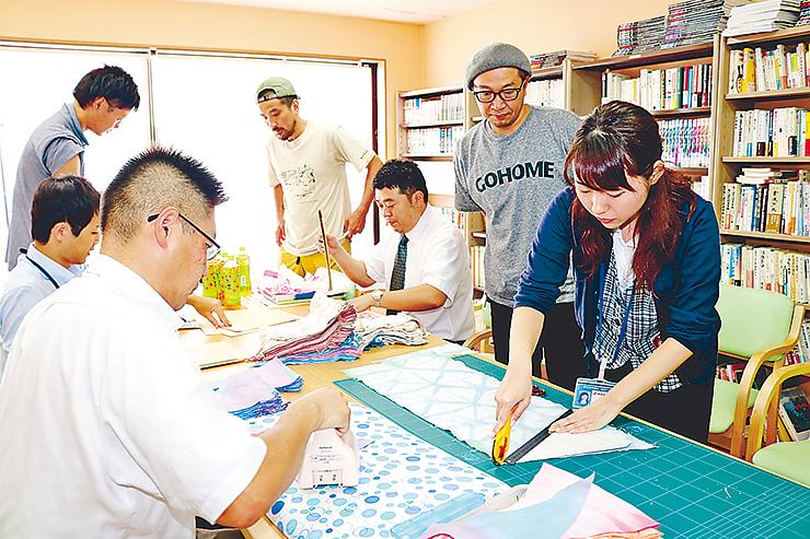 市六さん(右から2人目)が染めた布を使ってフラッグを作る実行委メンバーら