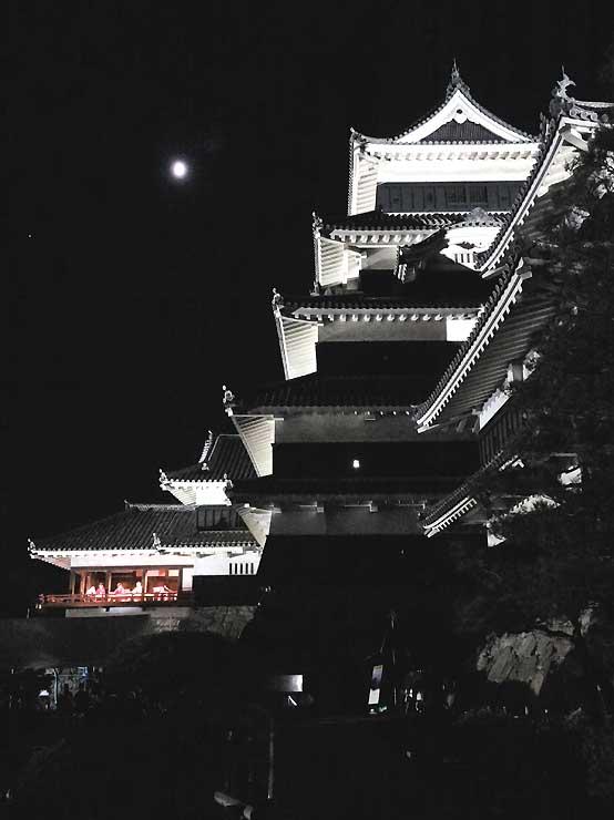 夜空に月が浮かぶ中、邦楽の演奏を楽しむ「月見の宴」が開かれた松本城=19日夜、松本市