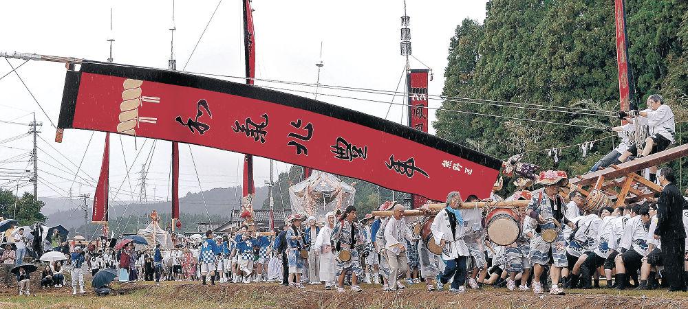 雨が降りしきる中、妙技「島田くずし」を披露する男衆=七尾市中島町谷内
