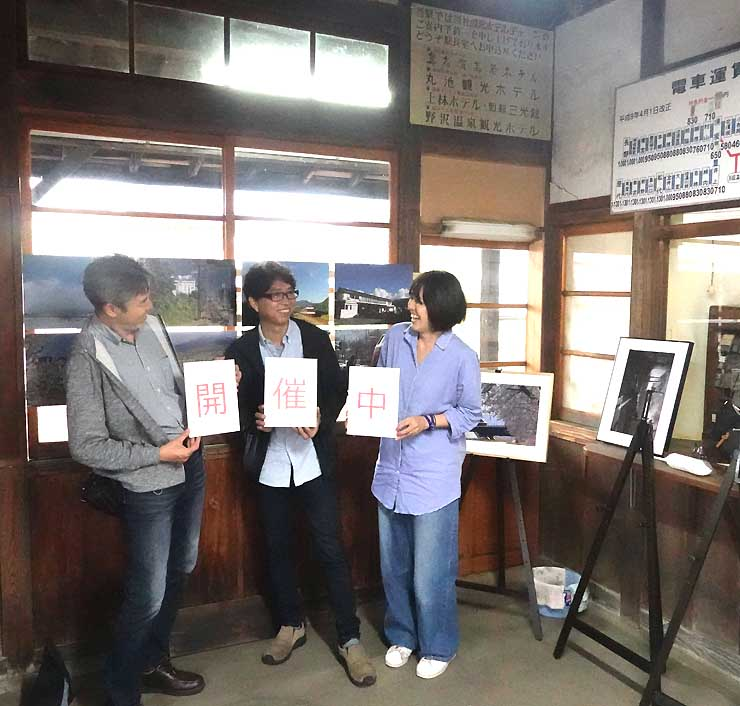 「開催中」というカードを持って写真展をPRする(右から)ヒノさん、米屋さん、直井さん