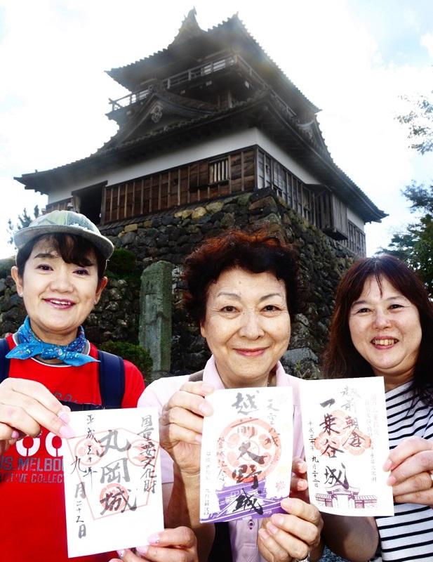三つの御朱印を手にするツアー客=9月22日、福井県坂井市の丸岡城