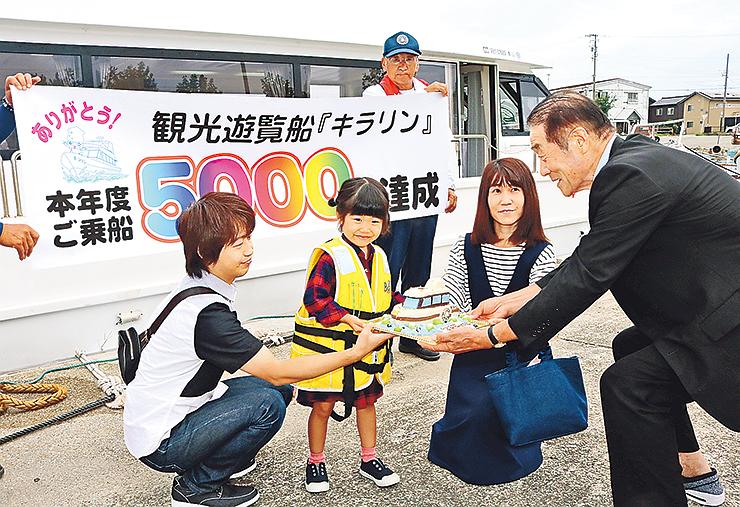 上田市長(右)からケーキを受け取る谷口さん一家