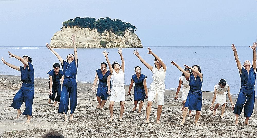 見附島を背景に力強い群舞を披露したタケイさんの公演=珠洲市の見付海岸