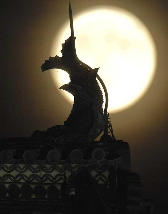 松本城天守のしゃちほこ越しに浮かぶ中秋の名月=24日午後6時53分、松本市
