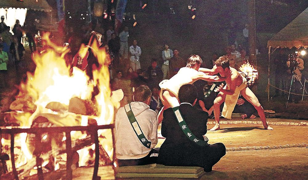 かがり火に照らされた土俵で行われた神事相撲=25日午後9時40分、羽咋市の唐戸山相撲場