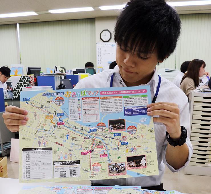 「新湊曳山まつり」の観覧おさんぽマップを持つ射水商議所の職員