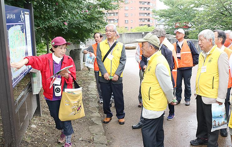 観光ボランティアガイド(左)の解説を聞いて散策する参加者=高岡古城公園