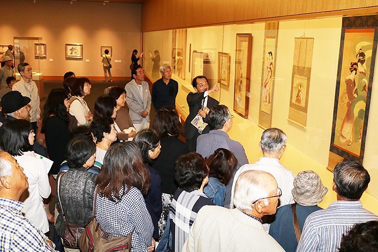 若松課長(中央)の解説を聞きながら、松園の「三美人之図」(右)に見入る来場者=県水墨美術館