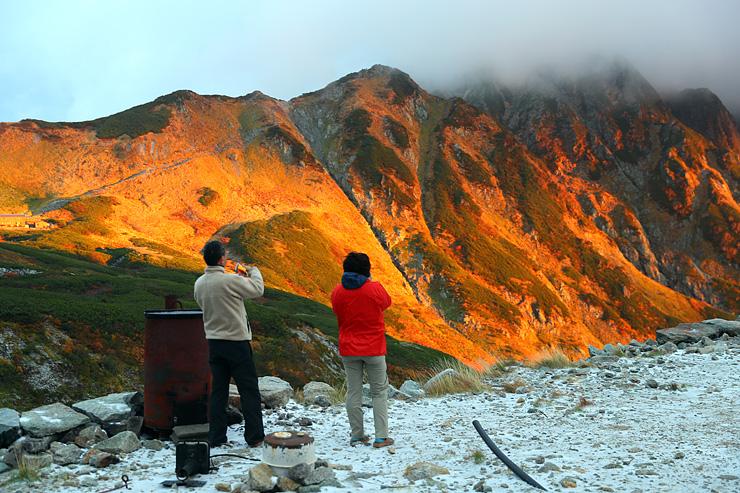 うっすらと雪が積もる剱沢小屋前で朝焼けに染まる剱岳を眺める登山者=2日午前5時45分ごろ、剱沢