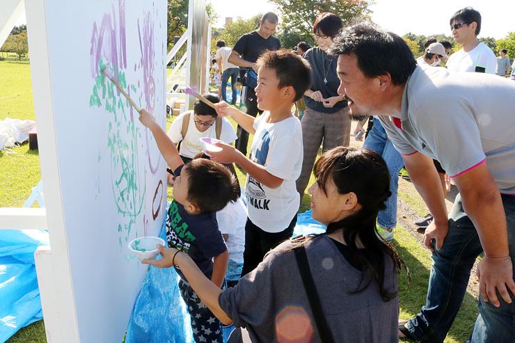大きなキャンバスに絵を描く子どもたち=稲荷公園