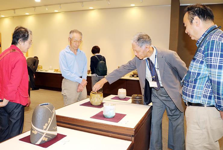 来場者に水指や花器を説明する加藤さん(右)と六渡会長(右から2人目)=富山大和