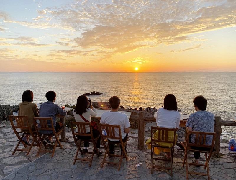 秋空と海をオレンジ色に染める夕日を眺めるカップルら=10月8日、福井県坂井市の東尋坊