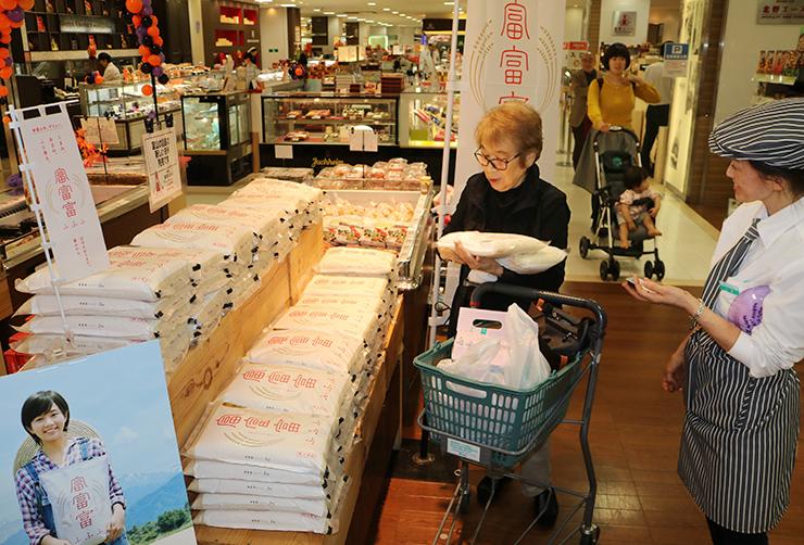 「富富富」の2キロ入り袋を手に取る買い物客=富山大和
