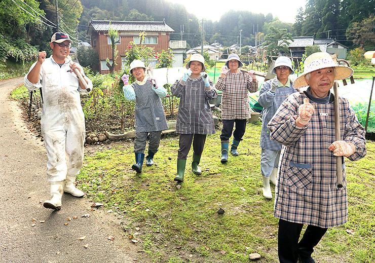稲垣さん(左)の指導に合わせ、ポーズを取る脇之谷内集落の女性グループ