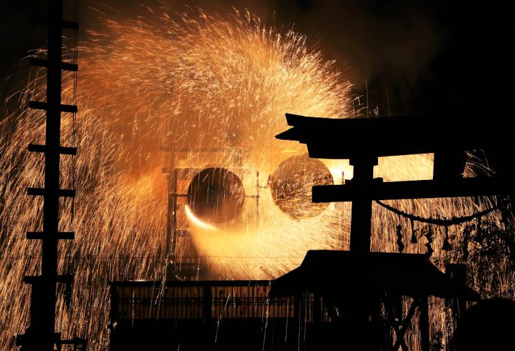 激しく回転しながら境内に火の粉を散らす仕掛け花火=13日午後9時1分、阿智村