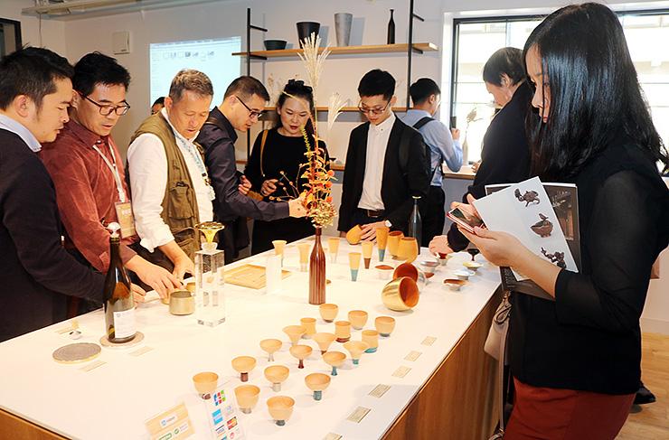 四津川製作所で製品のぐい飲みを手に取る中国からの視察団のメンバー=高岡市金屋町