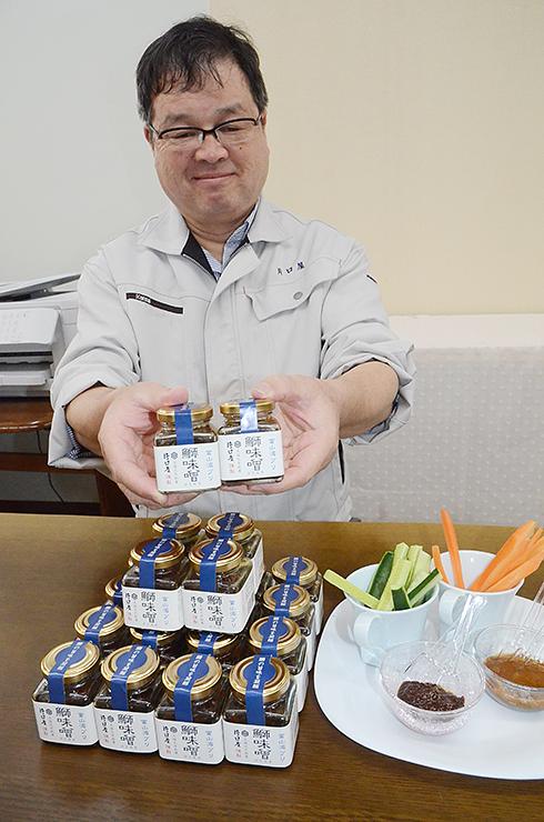 新たに開発した「鰤味噌」を手にする片口専務