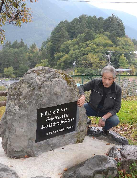 深田久弥が下栗の里について記した一文を刻んだ石碑を見る野牧さん