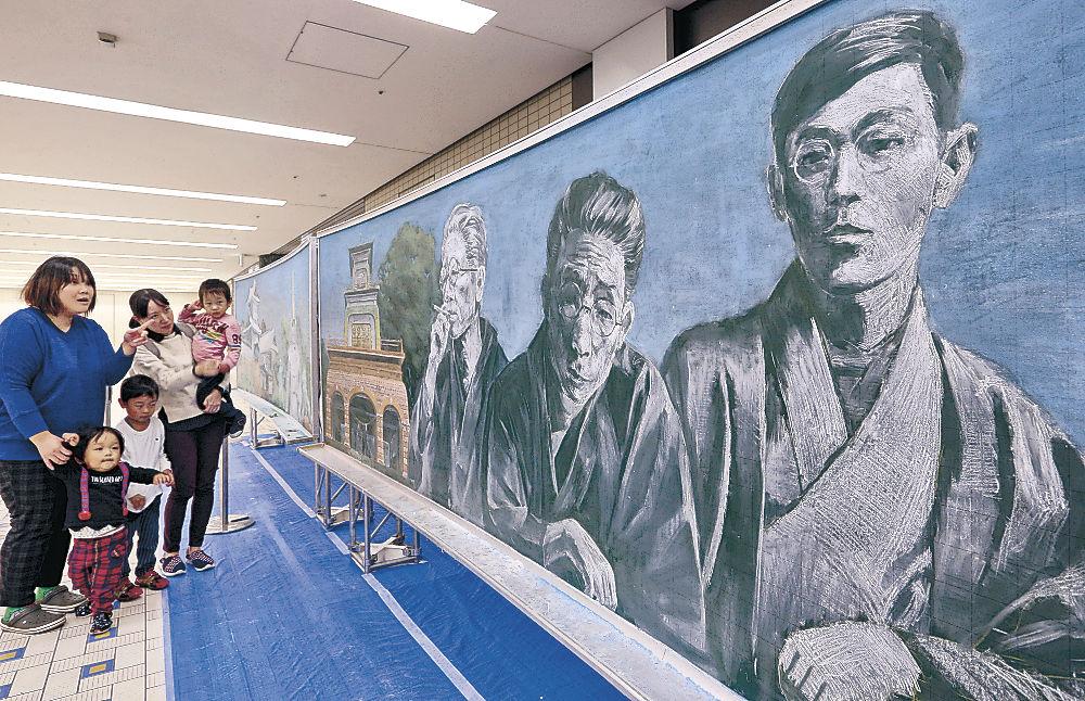 迫力ある三文豪が描かれた作品に見入る親子連れ=金沢駅もてなしドーム地下広場