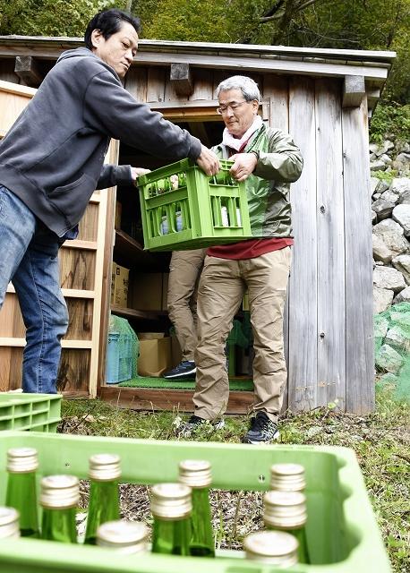 「荒島風穴」で貯蔵した日本酒を蔵出しする関係者=10月23日、福井県大野市の荒島岳