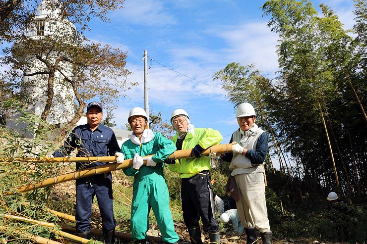 岩崎ノ鼻灯台(左奥)周辺で伐採した竹を運ぶ地元有志=高岡市伏木国分