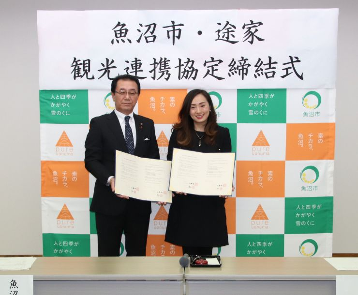観光連携協定を締結した途家の李珍妮・最高業務責任者(右)と佐藤雅一市長=魚沼市小出島