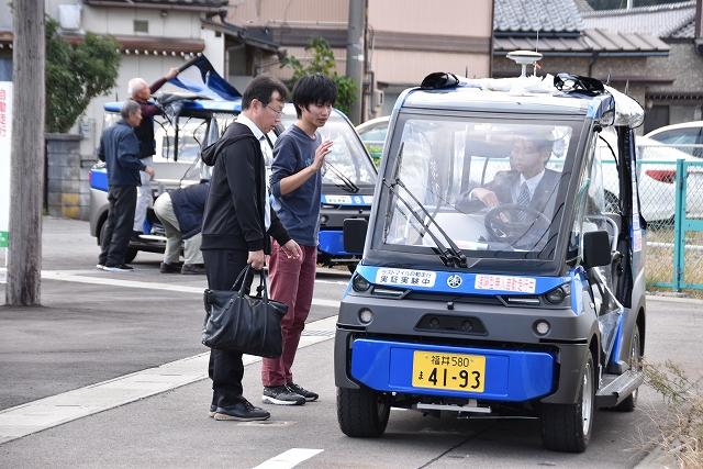 1カ月連続実証実験に備え車両試験を行う関係者=10月26日、福井県永平寺町東古市