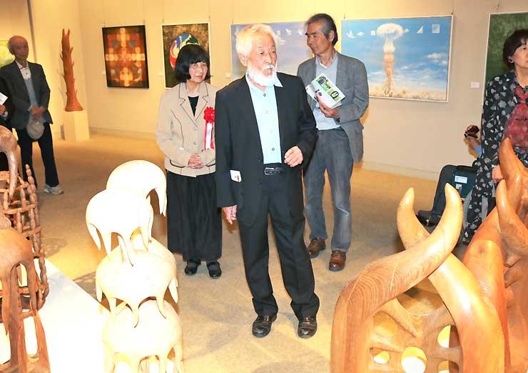 展示作品を解説する加藤邦彦さん(中央)と温子さん(中央左)