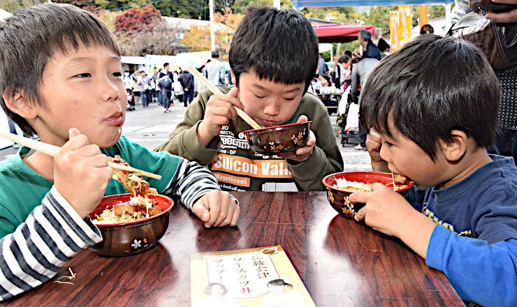 大勢が訪れたフェスの会場でソースかつ丼を頰張る子どもたち=27日、駒ケ根市